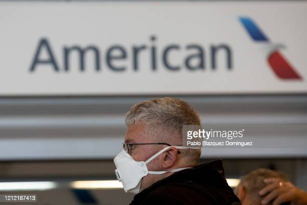 Passenger wearing protective mask queue at customer assistance of American Airlines before the Trump European travel ban goes into effect tonight at...