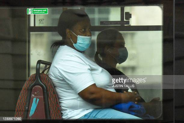 Passenger wears a face-mask as a Covid-19 protective measure as she travels on a bus in central London on July 14, 2021. - London Mayor Sadiq Khan on...