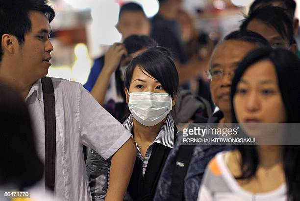 A passenger wears a mask at an arrival gate of the Suvarnabhumi airport in Bangkok on May 7 2009 The World Health Organisation urged Asian nations to...