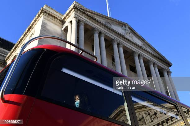 A passenger wears a protective face mask as she travels on an iconic London bus past the Bank of England in the City of London on March 11 as Britain...