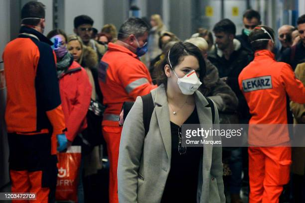 A passenger wears a surgical mask after a temperature check by health worker as she arrived from Milan Bergamo to Krakow International Airport on...