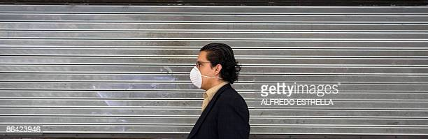 A passenger wears a surgical mask at Benito Suarez International Airport in Mexico City on May 5 2009 The impact of A influenza cost Mexico's economy...