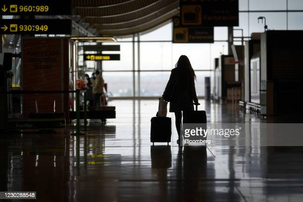 Passenger wheels a suitcase through a deserted arrivals hall at Madrid Barajas airport, operated by Aena SA, in Madrid, Spain, on Thursday, Dec. 24,...