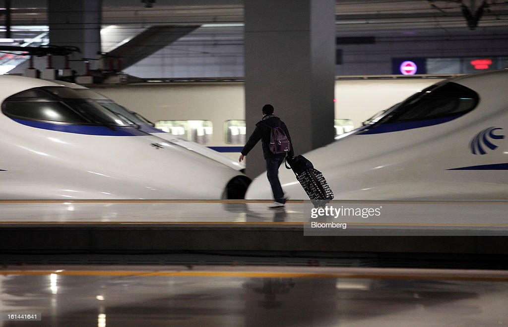 A passenger wheels his luggage past a China Railways high speed train at Hongqiao Railway Station in Shanghai, China, on Friday, Feb. 8, 2013. A record 3.41 billion passenger trips may be made this year during the Lunar New Year period, according to the National Development and Reform Commission. Photographer: Tomohiro Ohsumi/Bloomberg via Getty Images
