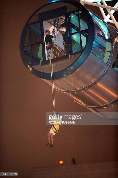 A passenger who was stuck in one of the capsules is lowered on the rope after the world's largest observation wheel the Singapore Flyer grounded to a...