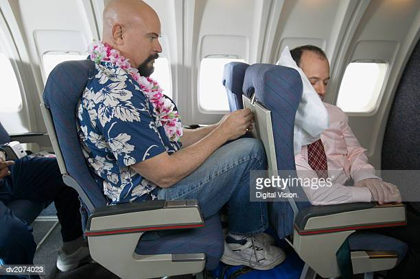 passenger with his knees against a sleeping businessman's chair on an aeroplane - uncomfortable stock pictures, royalty-free photos & images