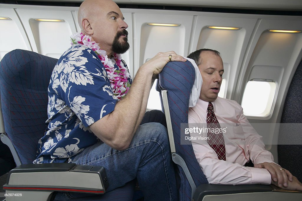 Passenger With His Knees Against a Sleeping Businessman's Chair on an Aeroplane : Stock Photo
