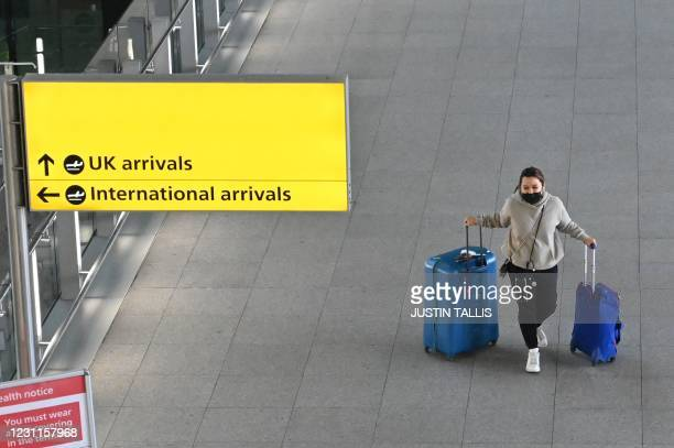 Passenger with luggage is seen at London Heathrow Airport in west London on February 14, 2021 . - A new 10-day hotel quarantine regime for British...