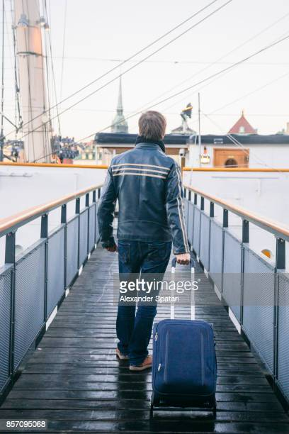 passenger with suitcase on wheels boarding a ship - passagier wasserfahrzeug stock-fotos und bilder