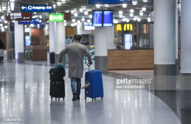 Passenger with suitcases walks at Duesseldorf Airport in Duesseldorf, western Germany, on December 21 amid the ongoing novel coronavirus / COVID-19...
