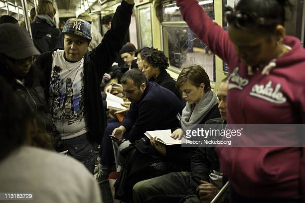 Passengers aboard a Brooklyn bound subway read, reflect and use hand held devices April 20, 2011 in New York.