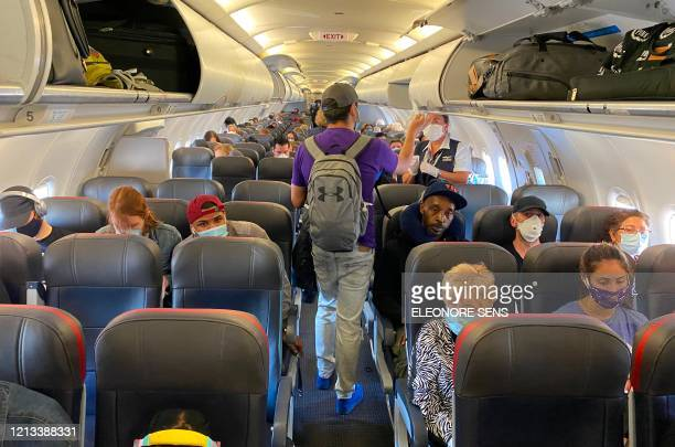 Passengers almost all wearing facemasks board an American Airlines flight to Charlotte on May 3 in New York City The wearing of masks to protect...