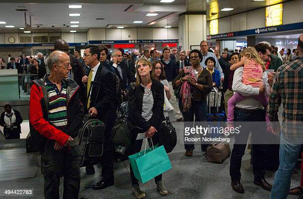Passengers and commuters wait for train departure information to be posted May 23 2014 at Pennsylvania Station in New York City