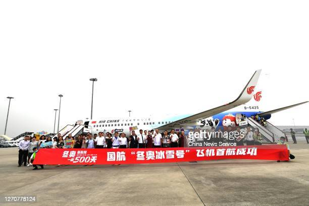 Passengers and crew members pose for photos in front of a newly painted Boeing 737 aircraft of Air China with patterns of the emblems and mascots of...