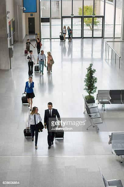 Passengers and crew walking through airport
