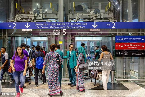 Passengers and Malaysian Airlines Bhd ground staff enter and exit elevators in the checkin hall at Kuala Lumpur International Airport in Sepang...