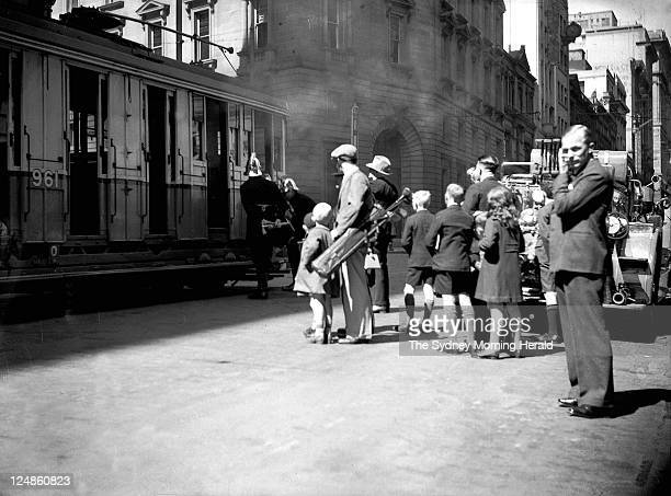 Passengers and pedestrians looking at a tram on fire on the corner of Hunter and Pitt Streets Sydney on 18 September 1948.