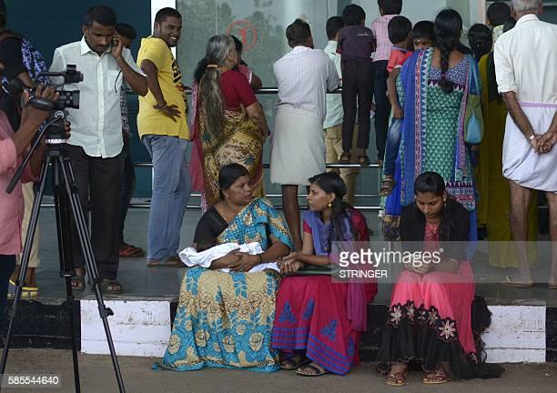 Passengers and relatives wait for news after hearing that the Emirates flight EK521 travelling from Thiruvananthapuram to Dubai crash landed at Dubai...