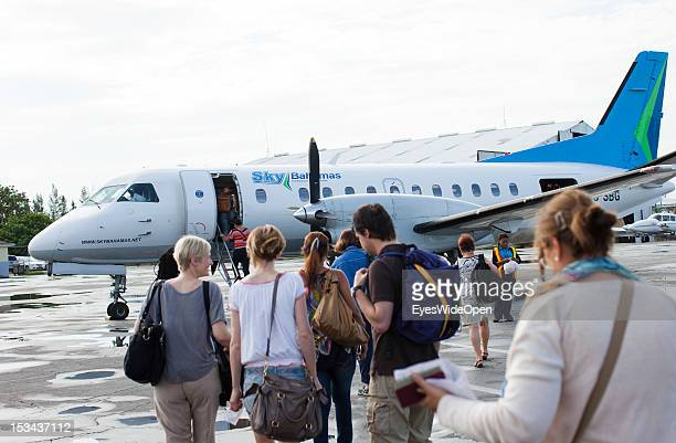 Passengers and tourists are walking on the airfield to an aircraft of the domestic and regional airline Sky Bahamas at Lynden Pindling International...