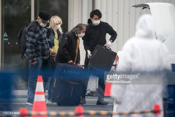 Passengers are assisted while loading bags into a taxi after disembarking from the quarantined Diamond Princess cruise ship docked at the Daikoku...