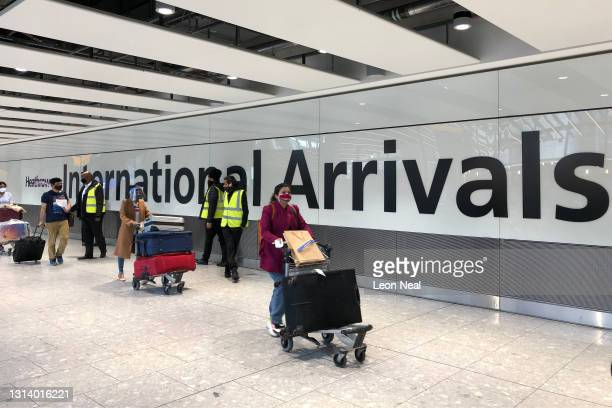 Passengers are escorted through the arrivals area of terminal 5 towards coaches destined for quarantine hotels, after landing at Heathrow airport on...