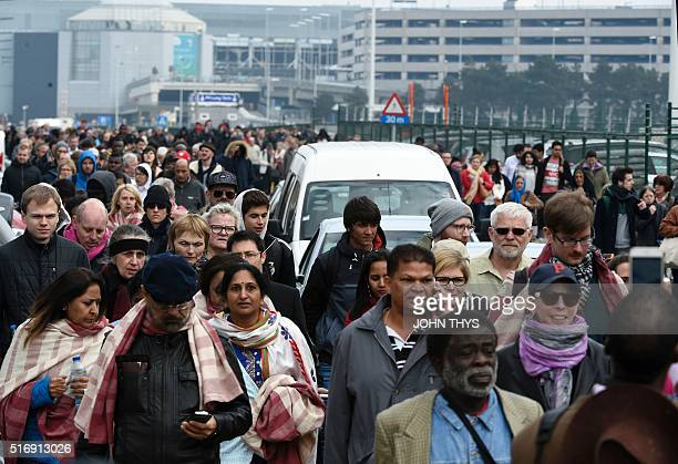TOPSHOT Passengers are evacuated from Brussels airport on March 22 2016 in Zaventem after at least 13 people were killed and 35 injured as twin...