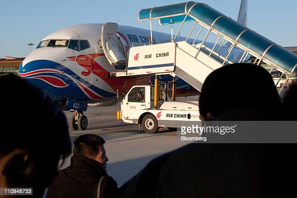 Passengers are ferried to an Air China Ltd flight at Beijing Capital International Airport in Beijing China on Thursday March 24 2011 Air China Ltd...