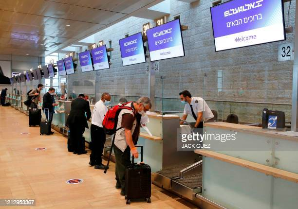 Passengers are pictured at a check-in counter in Ben Gurion Airport in Israel on May 14, 2020 as the airport gradually resumes operations with new...