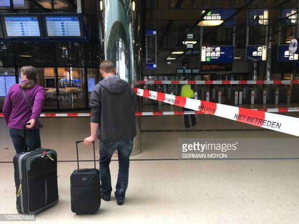Passengers are pictured in front of police cordon tape at The Central Railway Station in Amsterdam on August 31 after two people were hurt in a...
