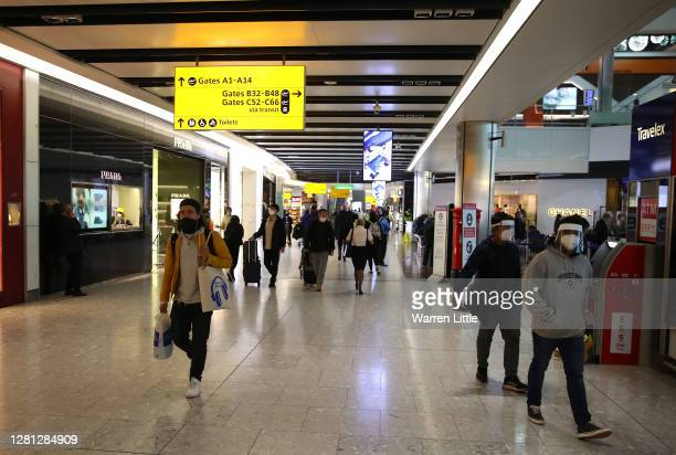 Passengers are pictured preparing to travel by air wearing protective masks on October 20 2020 at Heathrow Terminal 5 Airport in London United...