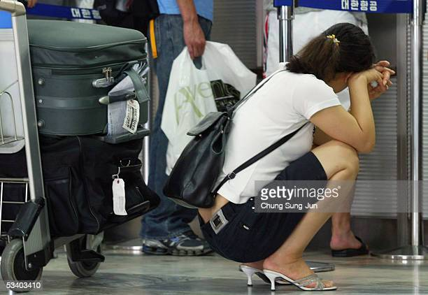 Passengers are seen at the Korean Air's ticket and checkin desk at Gimpo Airport on August 18 2005 in Seoul South Korea South Korea's largest airline...
