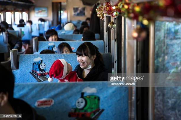 Passengers are seen in a carriage of Thomasthe Tank Engine standing on the platform of Shinkanaya Station during a preview of the Day out with...