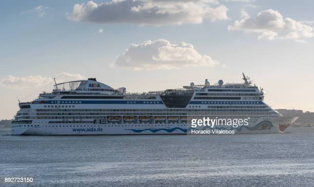 Passengers are seen on upper decks of AIDAblu a Sphinxclass cruise ship operated by the German cruise line AIDA Cruises as she sails on the Tagus...
