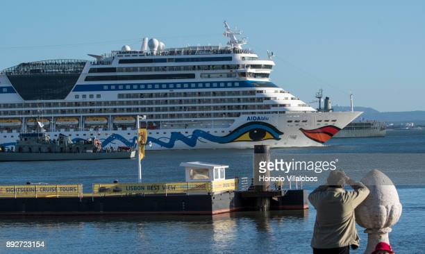 Passengers are seen on upper decks of AIDAblu a Sphinxclass cruise ship operated by the German cruise line AIDA Cruises as she sails off 'Lisbon...