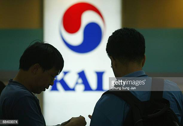 Passengers are seen stand at the Korean Airlines ticket and checkin desk at Gimpo Airport on August 18 2005 in Seoul South Korea South Korea's...