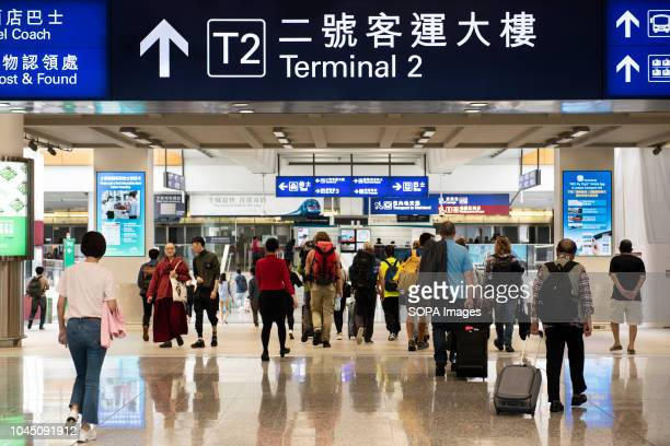 Passengers are seen walking through Hong Kong's terminal 1 exit where it connects with terminal 2 and MTR subway line to the city