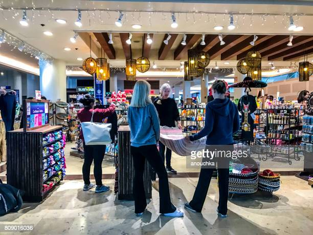 passengers are shopping in gift shop in cancun international airport, mexico - gift shop stock pictures, royalty-free photos & images