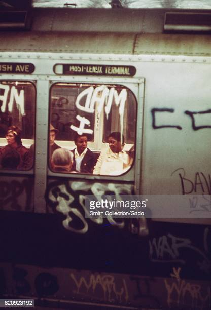 Passengers are visible through the window of a subway car which has been covered in graffiti, New York City, New York, May, 1974. Image courtesy...