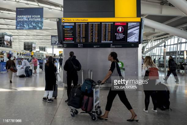 Passengers arrive at Heathrow Airport's Terminal 5 in west London on September 13 2019 British Airways has cancelled all its scheduled UK flights for...