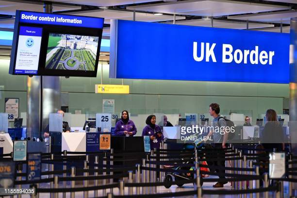 Passengers arrive at passport control in Terminal 2 at Heathrow Airport in London on July 16 2019
