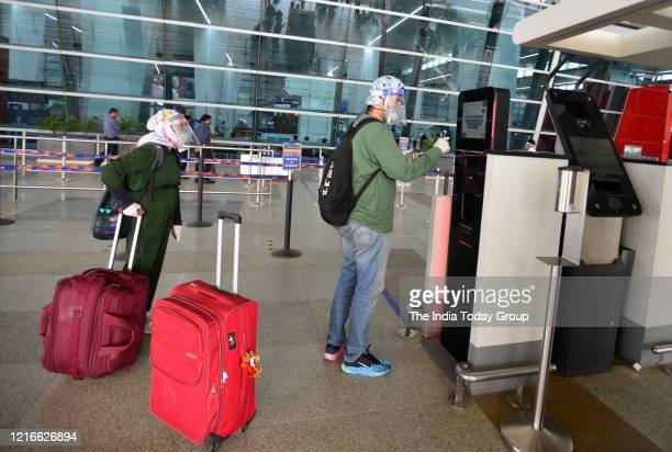 Passengers arrive at Terminal 3 of Indira Gandhi International Airport after domestic flight services were resumed during nationwide lockdown in New...