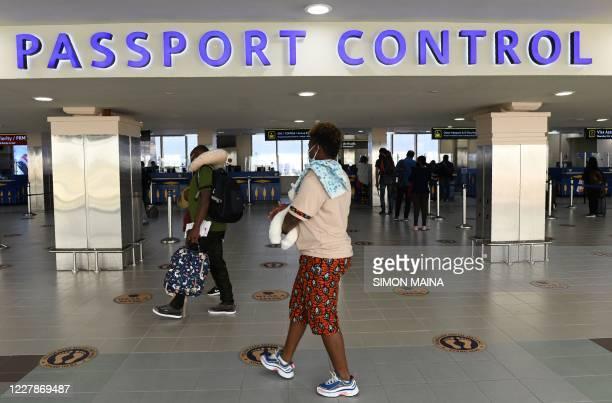 Passengers arrive at the Passport control section on August 1, 2020 at the Jomo Kenyatta international airport in Nairobi as Kenya Airways airline...
