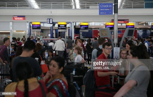 Passengers arrive with their luggage in Terminal 5 of London's Heathrow Airport on May 29 2017 Passengers faced a third day of disruption at Heathrow...