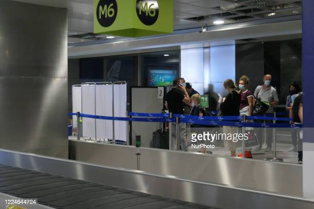Passengers arrived from Vienna, Austria wearing facemasks are checked for the county's entry form and are tested for Coronavirus at Thessaloniki...
