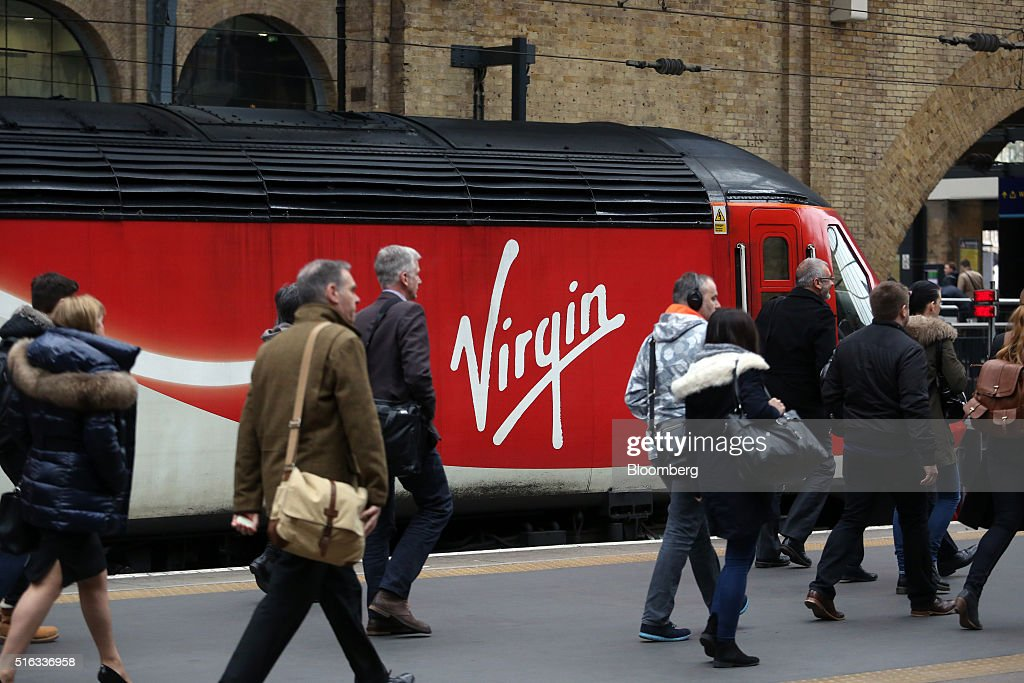 Passengers arriving at Kings Cross station pass a Virgin train standing on the platform in London, U.K., on Friday, March 18, 2016. Virgin Trains will revive plans to offer high-speed Internet access on Europes busiest rail route in a bid to beat the plane and persuade business people to travel outside peak hours. Photographer: Chris Ratcliffe/Bloomberg via Getty Images