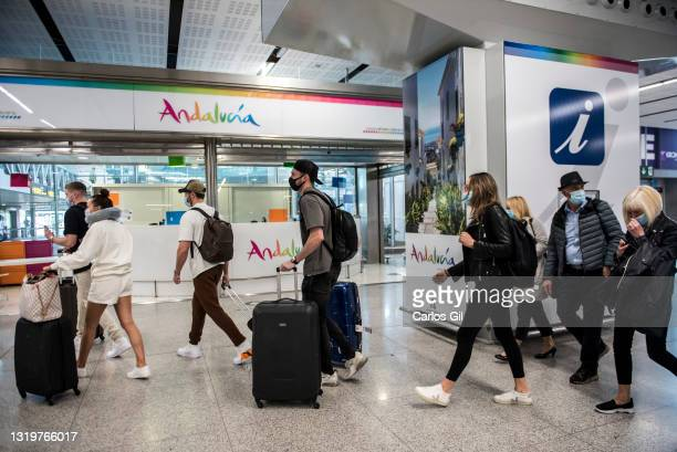 Passengers arriving from a London flight walk through the arrivals area of Malaga airport on May 24, 2021 in Malaga, Spain. From today, the Spanish...