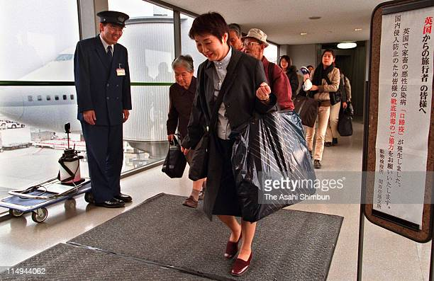 Passengers arriving from London walk on the disinfectant carpet to protect foot-and-mouth disease at Kansai International Airport on March 15, 2001...
