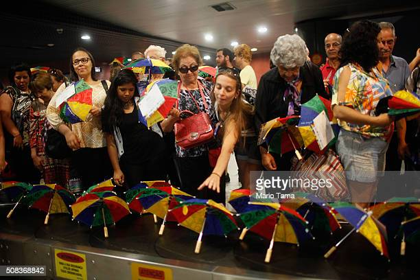 Passengers arriving in the baggage claim area at Guararapes Gilberto Freyre International Airport reach for Carnival umbrellas passed out as gifts on...