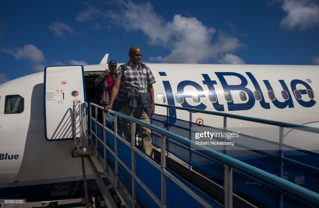Passengers arriving on a JetBlue Airways flight from New York walk down a ramp February 1, 2018 at the Maurice Bishop International Airport in St. George's, Grenada.