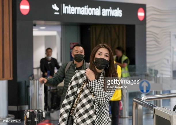 Passengers arriving on flights wear protective masks at the international airport on January 29, 2020 in Auckland, New Zealand. There have been no...